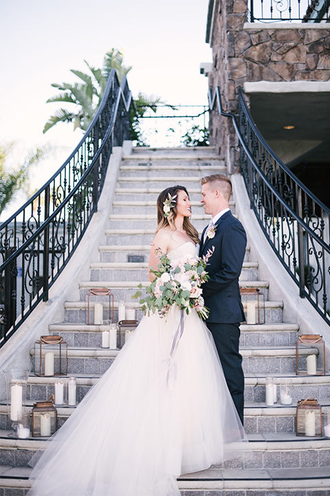 Orange county outdoor wedding at old ranch country club bride strapless ballgown with a sweetheart neckline and beaded detail with groom navy notch lapel suit with matching vest and white dress shirt with long silver tie and white floral boutonniere hugging and standing by stairs bride holding light pink and green floral bridal bouquet with candle decor