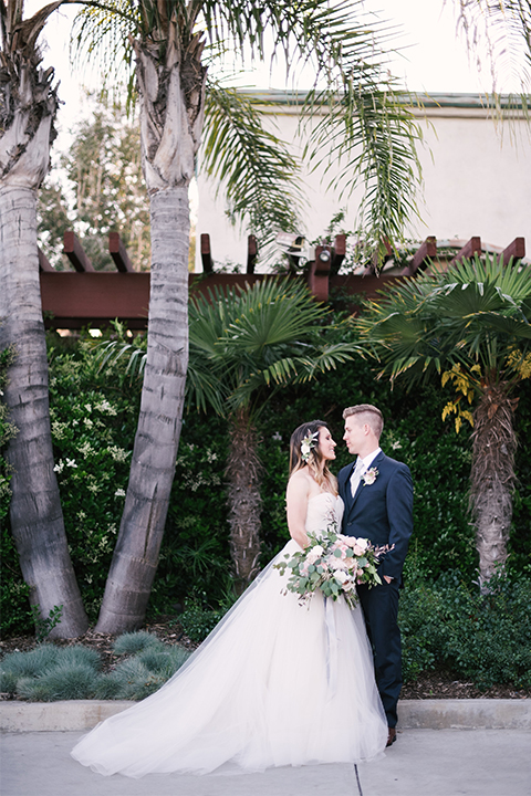 Orange county outdoor wedding at old ranch country club bride strapless ballgown with a sweetheart neckline and beaded detail with groom navy notch lapel suit with matching vest and white dress shirt with long silver tie and white floral boutonniere hugging and bride holding light pink and green floral bridal bouquet