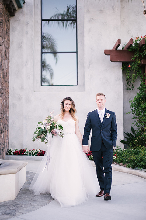 Orange county outdoor wedding at old ranch country club bride strapless ballgown with a sweetheart neckline and beaded detail with groom navy notch lapel suit with matching vest and white dress shirt with long silver tie and white floral boutonniere standing and holding hands bride holding light pink and green floral bridal bouquet