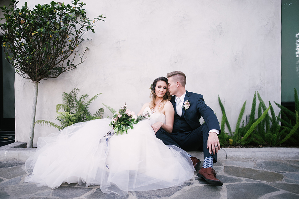 Orange county outdoor wedding at old ranch country club bride strapless ballgown with a sweetheart neckline and beaded detail with groom navy notch lapel suit with matching vest and white dress shirt with long silver tie and white floral boutonniere sitting and hugging bride holding light pink and green floral bridal bouquet