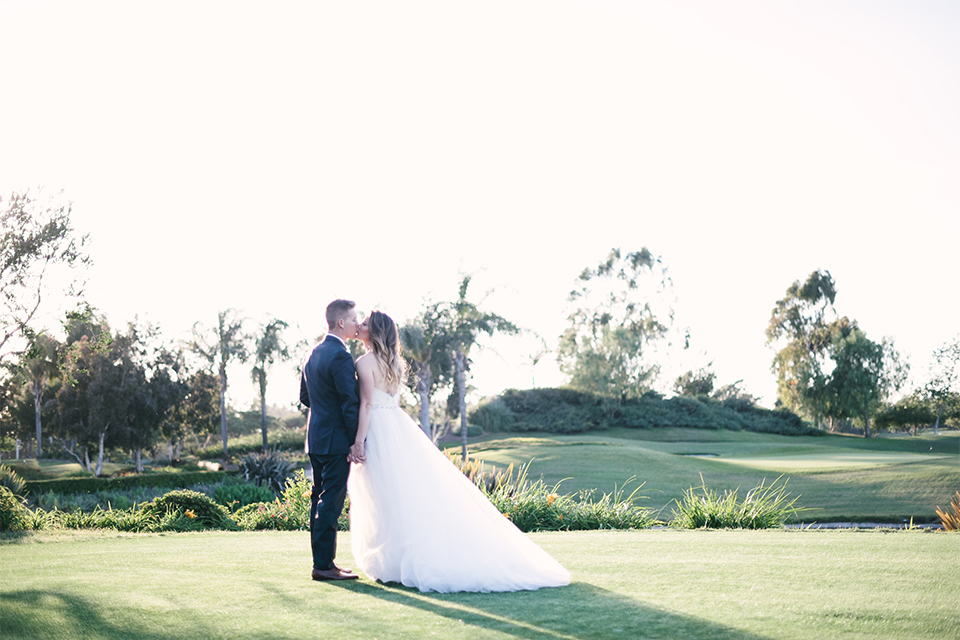 Orange county outdoor wedding at old ranch country club bride strapless ballgown with a sweetheart neckline and beaded detail with groom navy notch lapel suit with matching vest and white dress shirt with long silver tie and white floral boutonniere kissing