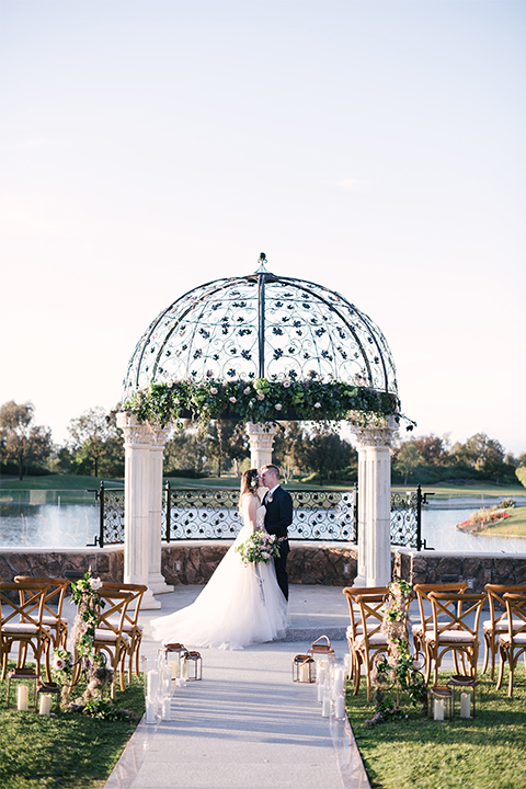 Orange county outdoor wedding at old ranch country club bride strapless ballgown with a sweetheart neckline and beaded detail with groom navy notch lapel suit with matching vest and white dress shirt with long silver tie and white floral boutonniere standing during ceremony bride holding light pink and green floral bridal bouquet