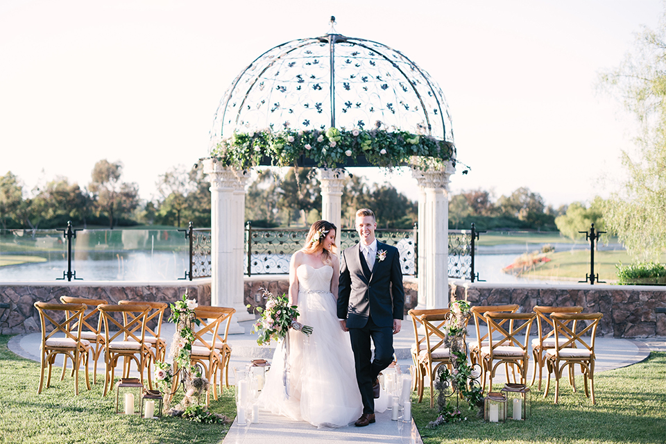 Orange county outdoor wedding at old ranch country club bride strapless ballgown with a sweetheart neckline and beaded detail with groom navy notch lapel suit with matching vest and white dress shirt with long silver tie and white floral boutonniere walking down aisle after ceremony bride holding light pink and green floral bridal bouquet