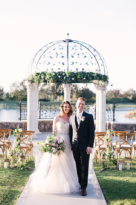 Orange county outdoor wedding at old ranch country club bride strapless ballgown with a sweetheart neckline and beaded detail with groom navy notch lapel suit with matching vest and white dress shirt with long silver tie and white floral boutonniere standing in aisle during ceremony bride holding light pink and green floral bridal bouquet