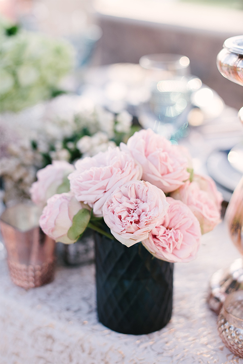 Orange county outdoor wedding shoot at old ranch country club table set up light silver table linen with white and grey place settings with navy blue napkin linen decor with clear wine glasses and dark blue designed glasses with light pink flower centerpiece decor with candles