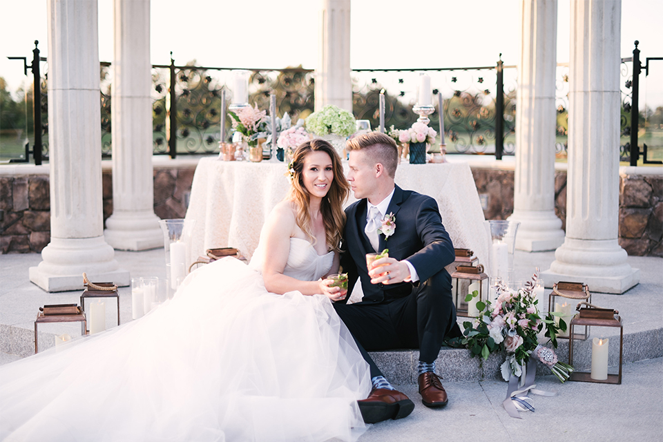 Orange county outdoor wedding at old ranch country club bride strapless ballgown with a sweetheart neckline and beaded detail with groom navy notch lapel suit with matching vest and white dress shirt with long silver tie and white floral boutonniere sitting by table holding drinks