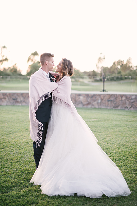 Orange county outdoor wedding at old ranch country club bride strapless ballgown with a sweetheart neckline and beaded detail with groom navy notch lapel suit with matching vest and white dress shirt with long silver tie and white floral boutonniere hugging with blanket wrapped around