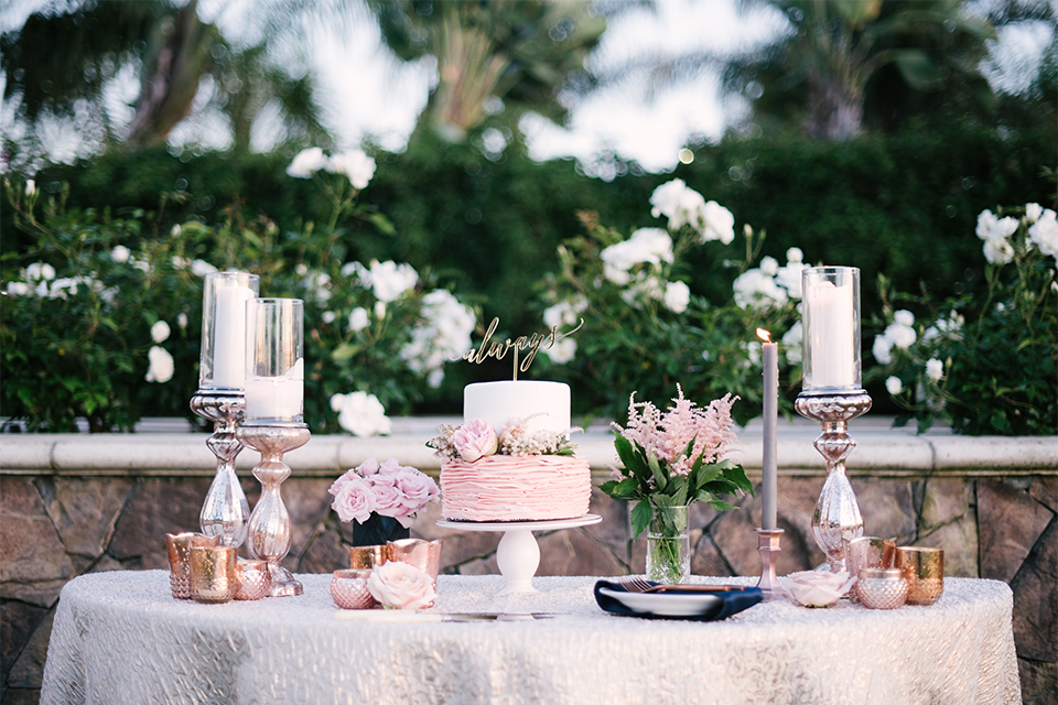 Orange county outdoor wedding shoot at old ranch country club wedding cake and dessert table two tier white and pink wedding cake with calligraphy cake topper and tall white candles with smaller candles and pink flower decor on white table linen