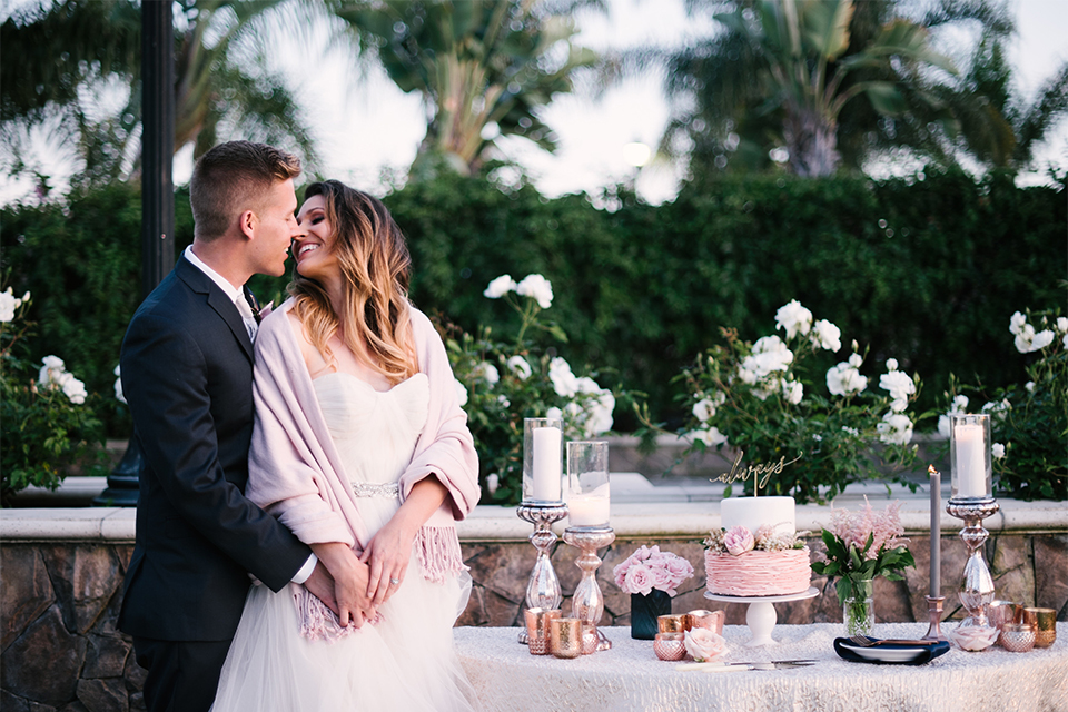 Orange county outdoor wedding at old ranch country club bride strapless ballgown with a sweetheart neckline and beaded detail with groom navy notch lapel suit with matching vest and white dress shirt with long silver tie and white floral boutonniere standing by cake table