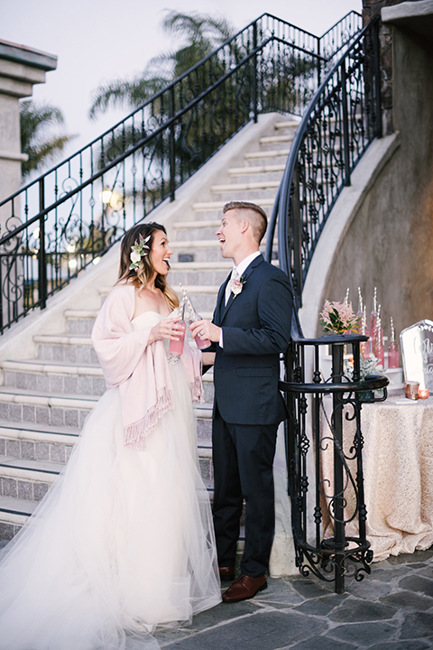 Orange county outdoor wedding at old ranch country club bride strapless ballgown with a sweetheart neckline and beaded detail with groom navy notch lapel suit with matching vest and white dress shirt with long silver tie and white floral boutonniere standing by stairs holding pink drinks