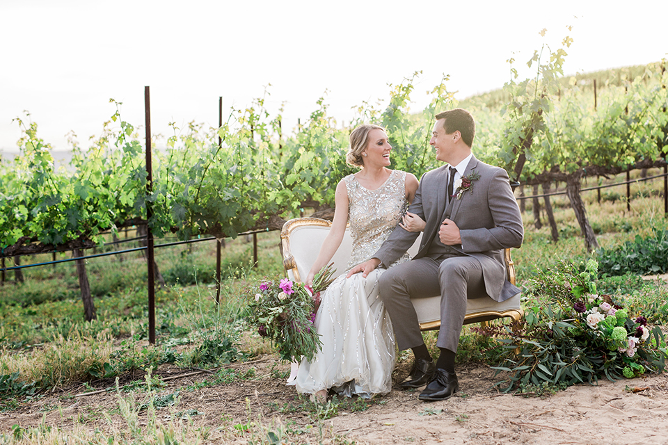 Temecula outdoor wedding at callaway winery bride form fitting lace gown with crystal beading and lace detail with open back design and beaded straps with groom grey notch lapel suit with matching vest and white dress shirt with long black skinny tie and pink floral boutonniere sitting on white vintage couch and bride holding pink and green floral bridal bouquet