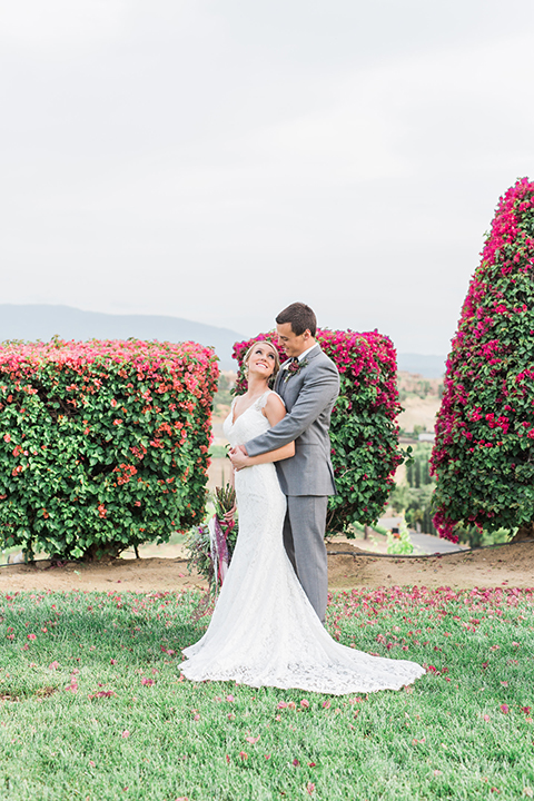 Temecula outdoor wedding at callaway winery bride form fitting lace gown with crystal beading and lace detail with open back design and beaded straps with groom grey notch lapel suit with matching vest and white dress shirt with long black skinny tie and pink floral boutonniere hugging