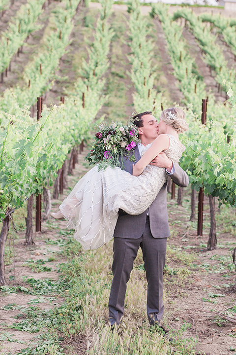 Temecula outdoor wedding at callaway winery bride form fitting lace gown with crystal beading and lace detail with open back design and beaded straps with groom grey notch lapel suit with matching vest and white dress shirt with long black skinny tie and pink floral boutonniere kissing and bride holding pink and green floral bridal bouquet