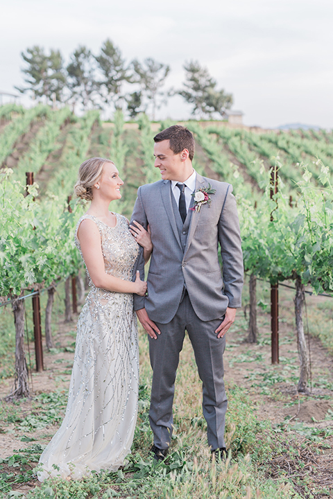 Temecula outdoor wedding at callaway winery bride form fitting lace gown with crystal beading and lace detail with open back design and beaded straps with groom grey notch lapel suit with matching vest and white dress shirt with long black skinny tie and pink floral boutonniere holding hands