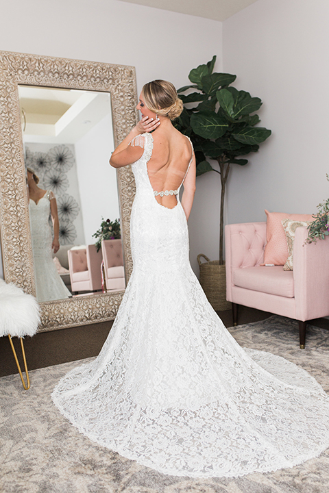Temecula outdoor wedding at callaway winery bride form fitting lace gown with crystal beading and lace detail with open back design and beaded straps looking in mirror getting ready before ceremony