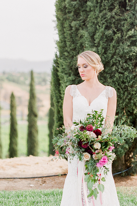 Temecula outdoor wedding at callaway winery bride form fitting lace gown with crystal beading and lace detail with open back design and beaded straps holding pink and green floral bridal bouquet
