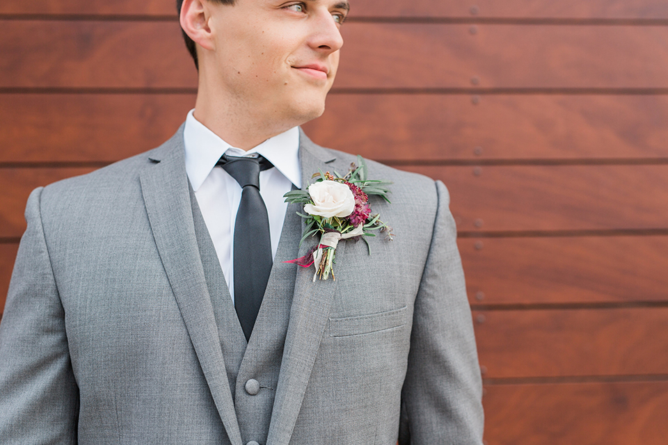 Temecula outdoor wedding at callaway winery groom grey notch lapel suit with matching vest and white dress shirt with long black skinny tie and white and pink floral boutonniere