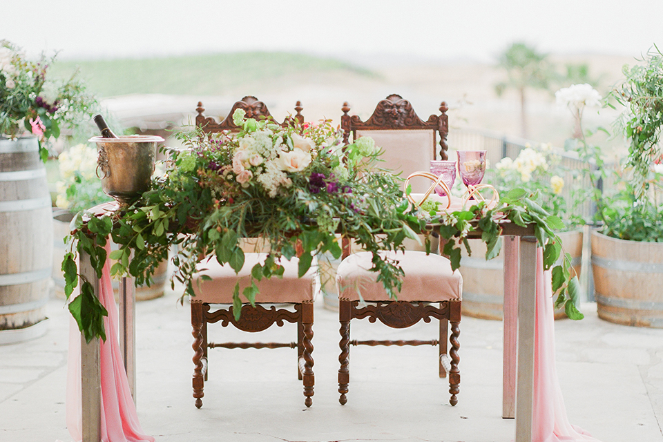 Temecula outdoor wedding at callaway winery table set up light brown wood table with blush pink table runner and white and green flower centerpiece decor with white and gold place settings with blush pink napkins and white and brown vintage chairs