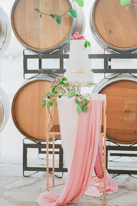 Temecula outdoor wedding at callaway winery wedding cake three tier white cake with pink flower decor on top and greenery floral decor on side with blush pink table linen decor and wine barrels in background wedding photo idea for cake