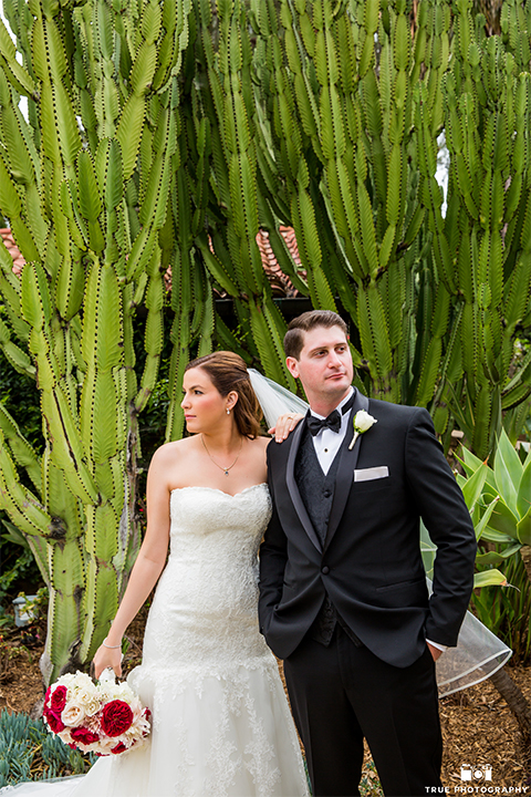 San diego beach wedding at estancia la jolla bride form fitting strapless gown with sweetheart neckline and lace design with long veil and groom black shawl lapel tuxedo with matching vest and white dress shirt with black bow tie and white pocket square with white floral boutonniere hugging and bride holding white and red floral bridal bouquet