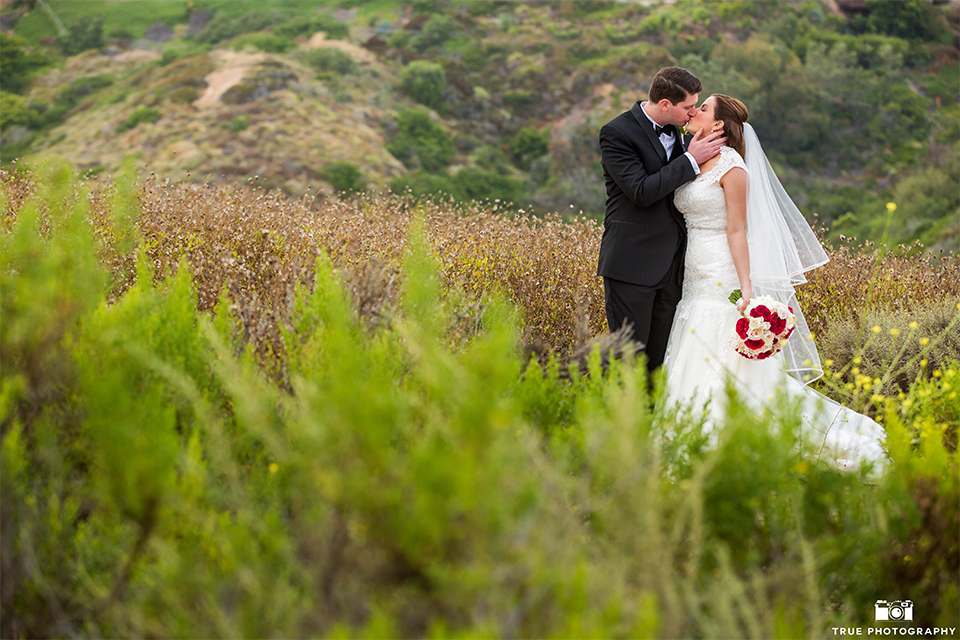 San diego beach wedding at estancia la jolla bride form fitting strapless gown with sweetheart neckline and lace design with long veil and groom black shawl lapel tuxedo with matching vest and white dress shirt with black bow tie and white pocket square with white floral boutonniere kissing and bride holding white and red floral bridal bouquet