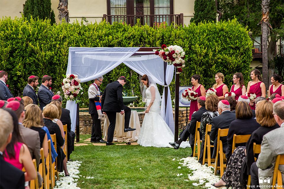 San diego beach wedding at estancia la jolla bride form fitting strapless gown with sweetheart neckline and lace design with long veil and groom black shawl lapel tuxedo with matching vest and white dress shirt with black bow tie and white pocket square with white floral boutonniere ceremony
