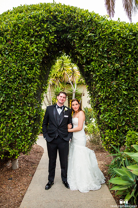 San diego beach wedding at estancia la jolla bride form fitting strapless gown with sweetheart neckline and lace design with long veil and groom black shawl lapel tuxedo with matching vest and white dress shirt with black bow tie and white pocket square with white floral boutonniere holding hands