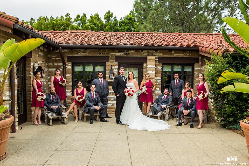 San diego beach wedding at estancia la jolla bride form fitting strapless gown with sweetheart neckline and lace design with long veil and groom black shawl lapel tuxedo with matching vest and white dress shirt with black bow tie and white pocket square with white floral boutonniere with wedding party bridesmaids short red dresses and groomsmen charcoal grey suits with long red ties