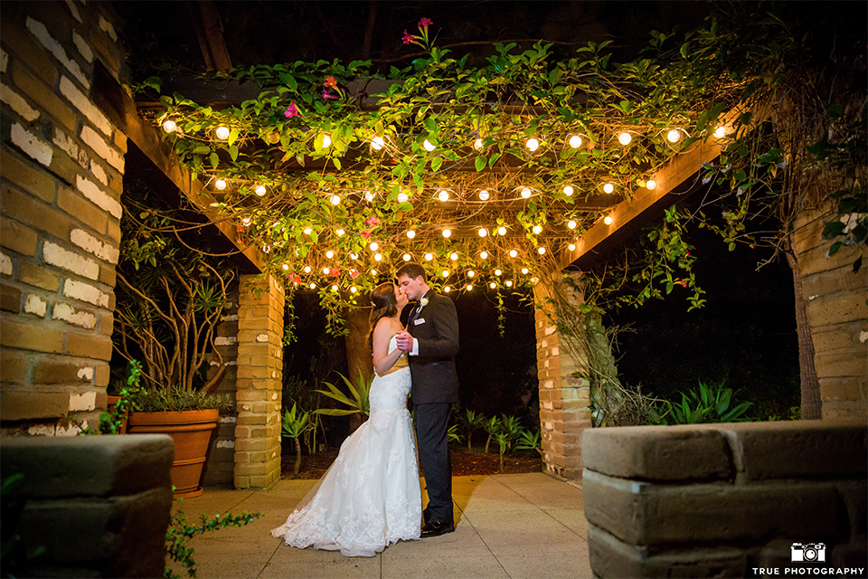 San diego beach wedding at estancia la jolla bride form fitting strapless gown with sweetheart neckline and lace design with long veil and groom black shawl lapel tuxedo with matching vest and white dress shirt with black bow tie and white pocket square with white floral boutonniere dancing under lights