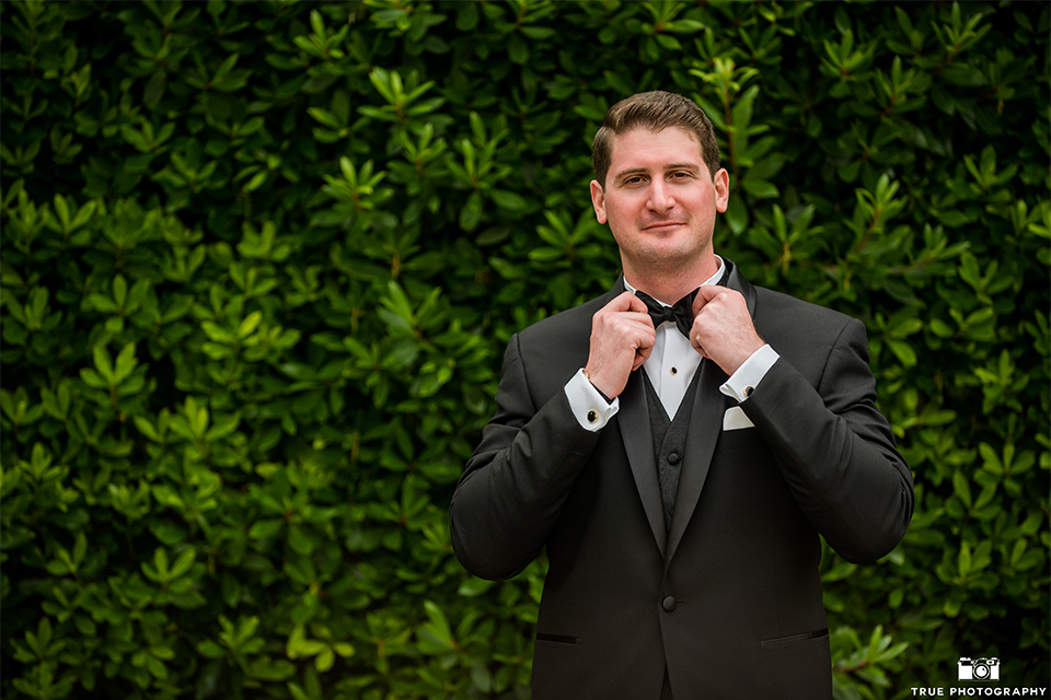 San diego beach wedding at estancia la jolla groom black shawl lapel tuxedo with black bow tie and white dress shirt with white pocket square and white floral boutonniere fixing tie