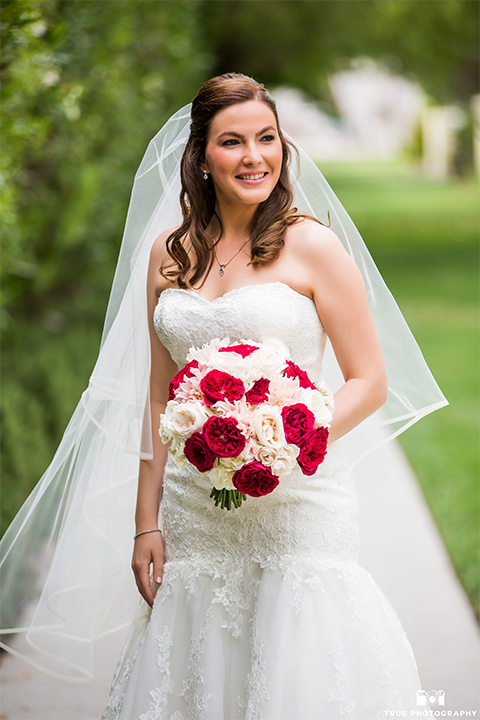 San diego beach wedding at estancia la jolla bride form fitting strapless gown with sweetheart neckline and lace design with long veil holding white and red floral bridal bouquet