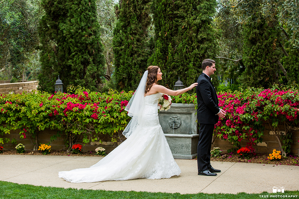 San diego beach wedding at estancia la jolla bride form fitting strapless gown with sweetheart neckline and lace design with long veil and groom black shawl lapel tuxedo with matching vest and white dress shirt with black bow tie and white pocket square with white floral boutonniere first look