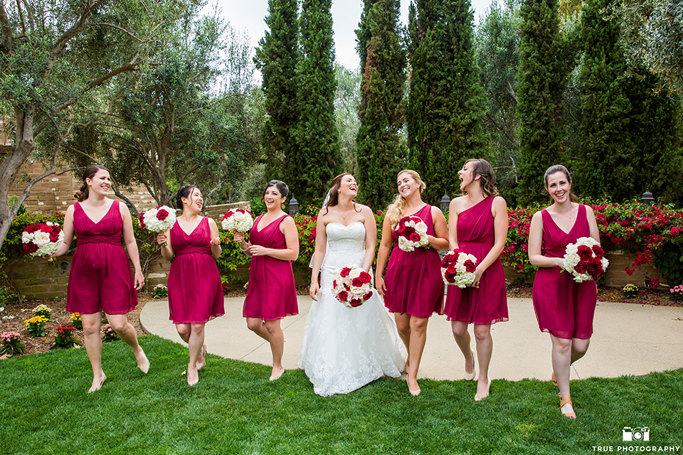San diego beach wedding at estancia la jolla bride form fitting strapless gown with sweetheart neckline and lace design with long veil holding white and red floral bridal bouquet with bridesmaids short red dresses holding white and red floral bridal bouquets walking