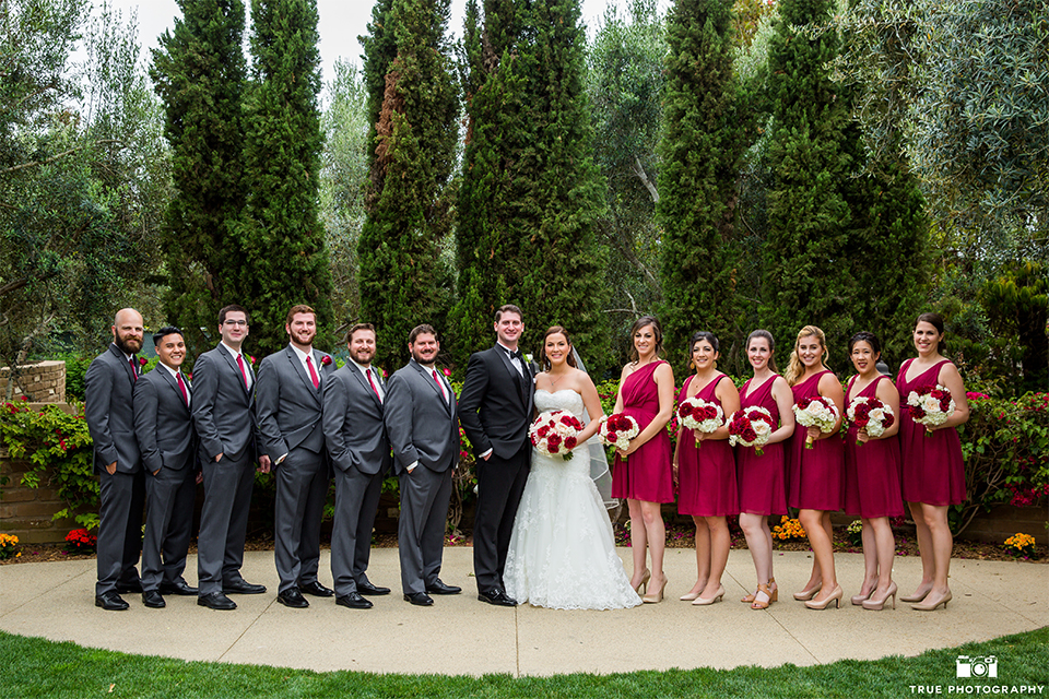 San diego beach wedding at estancia la jolla bride form fitting strapless gown with sweetheart neckline and lace design with long veil and groom black shawl lapel tuxedo with matching vest and white dress shirt with black bow tie and white pocket square with white floral boutonniere with bridesmaids short red dresses and white and red floral bouquets and groomsmen charcoal grey suits with long red ties