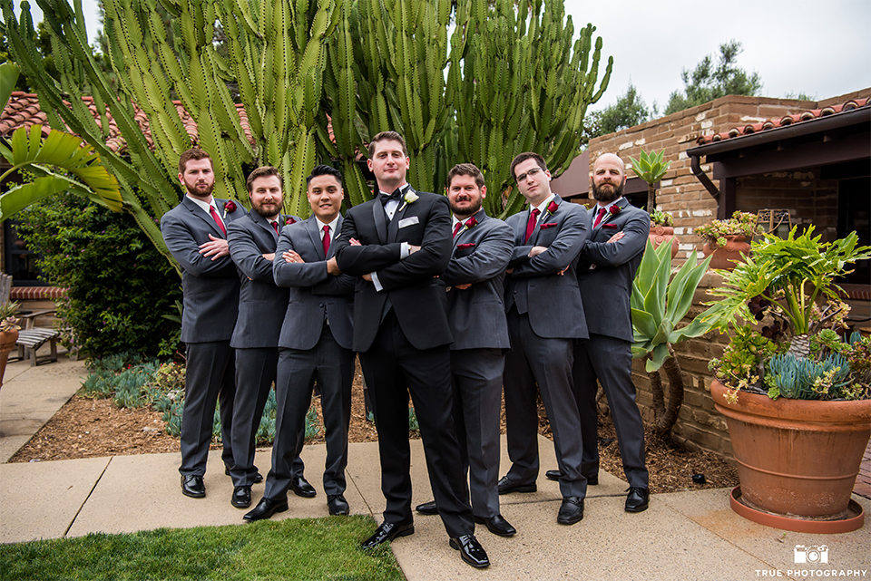 San diego beach wedding at estancia la jolla groom black shawl lapel tuxedo with black bow tie and white dress shirt with white pocket square and white floral boutonniere with groomsmen charcoal grey suits with long red ties