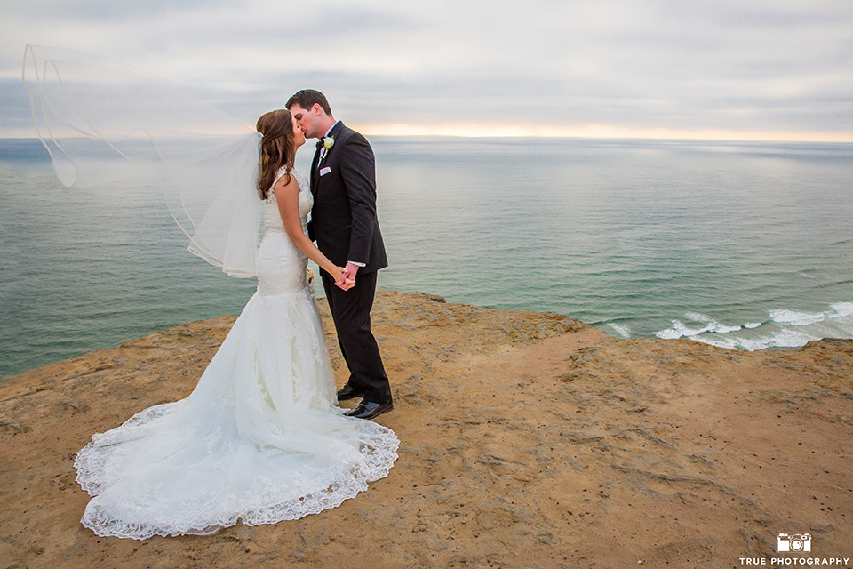 San diego beach wedding at estancia la jolla bride form fitting strapless gown with sweetheart neckline and lace design with long veil and groom black shawl lapel tuxedo with matching vest and white dress shirt with black bow tie and white pocket square with white floral boutonniere holding hands and kissing