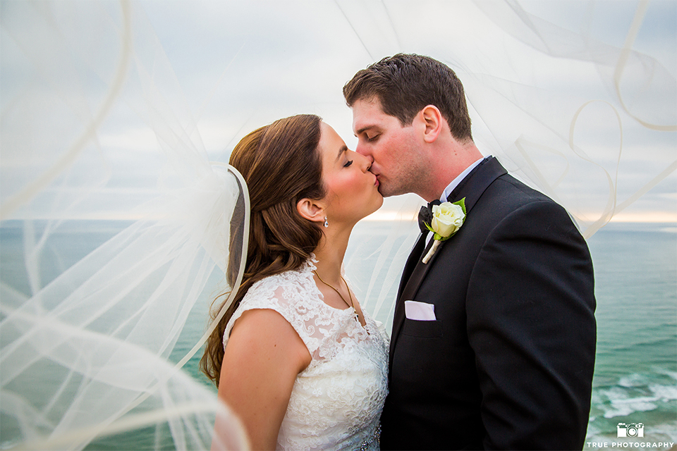 San diego beach wedding at estancia la jolla bride form fitting strapless gown with sweetheart neckline and lace design with long veil and groom black shawl lapel tuxedo with matching vest and white dress shirt with black bow tie and white pocket square with white floral boutonniere kissing under veil close up