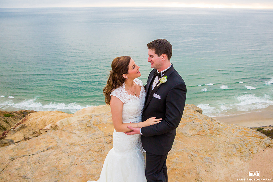 San diego beach wedding at estancia la jolla bride form fitting strapless gown with sweetheart neckline and lace design with long veil and groom black shawl lapel tuxedo with matching vest and white dress shirt with black bow tie and white pocket square with white floral boutonniere hugging