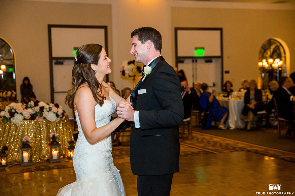 San diego beach wedding at estancia la jolla bride form fitting strapless gown with sweetheart neckline and lace design with long veil and groom black shawl lapel tuxedo with matching vest and white dress shirt with black bow tie and white pocket square with white floral boutonniere first dance