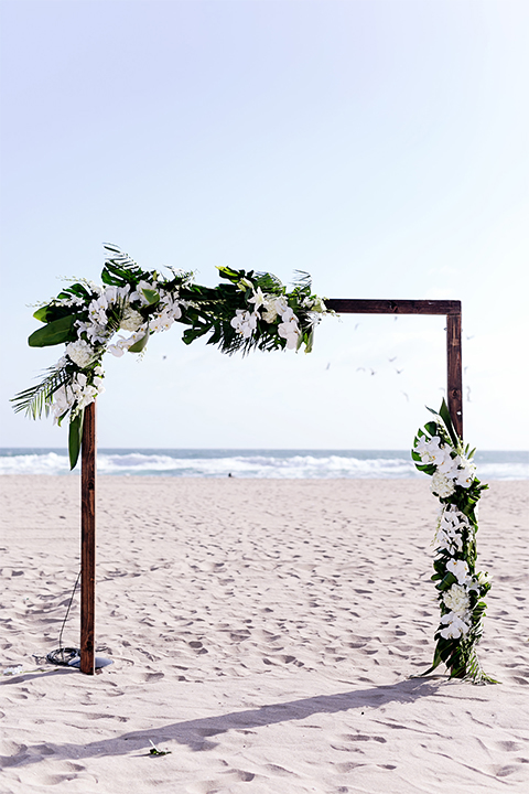 Huntington beach wedding at the hilton waterfront resort wedding ceremony altar with brown wood and white and green flower decor on sand wedding photo idea for ceremony altar