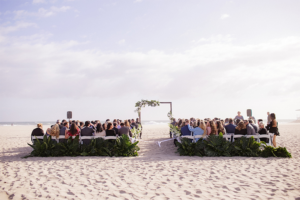 Huntington beach wedding at the hilton waterfront resort wedding ceremony altar with brown wood and white and green flower decor on sand wedding photo idea for ceremony altar with guests sitting in chairs for ceremony