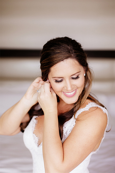 Huntington beach wedding at the hilton waterfront resort bride form fitting lace gown with a plunging neckline and thin straps with lace detail and low back design