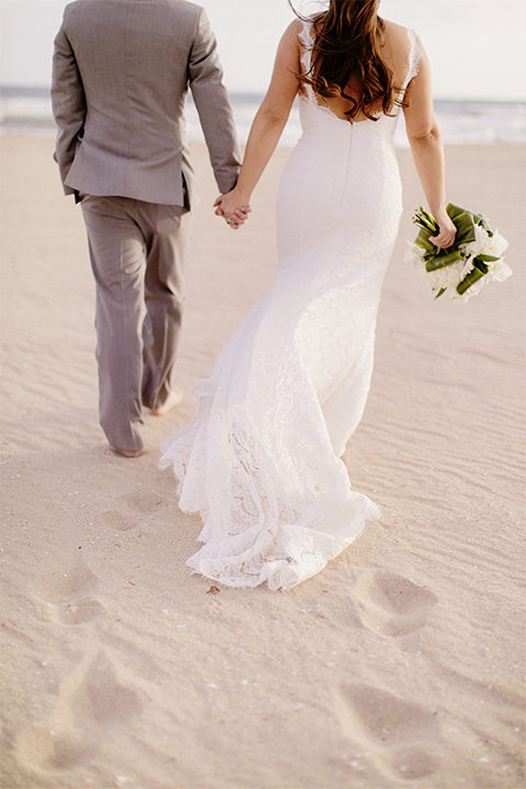 Huntington beach wedding at the hilton waterfront resort bride form fitting lace gown with a plunging neckline and thin straps with lace detail and low back design with groom heather grey notch lapel suit with matching vest and white dress shirt with long navy blue patterned tie and white floral boutonniere holding hands and bride holding white and green floral bridal bouquet