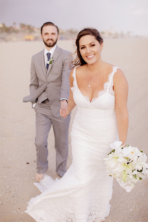 Huntington beach wedding at the hilton waterfront resort bride form fitting lace gown with a plunging neckline and thin straps with lace detail and low back design with groom heather grey notch lapel suit with matching vest and white dress shirt with long navy blue patterned tie and white floral boutonniere holding hands and walking bride holding white and green floral bridal boquuet