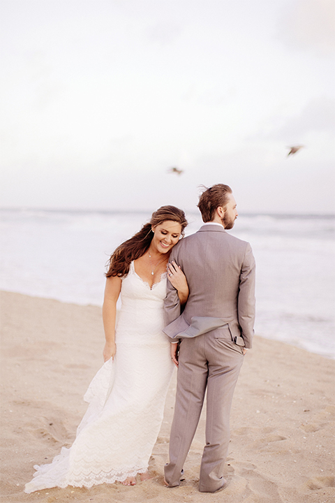 Huntington beach wedding at the hilton waterfront resort bride form fitting lace gown with a plunging neckline and thin straps with lace detail and low back design with groom heather grey notch lapel suit with matching vest and white dress shirt with long navy blue patterned tie and white floral boutonniere standing and hugging arm bride holding white and green floral bridal bouquet