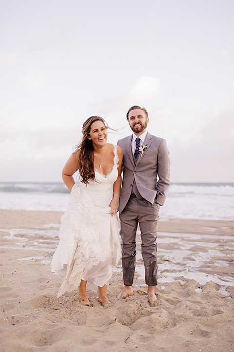 Huntington beach wedding at the hilton waterfront resort bride form fitting lace gown with a plunging neckline and thin straps with lace detail and low back design with groom heather grey notch lapel suit with matching vest and white dress shirt with long navy blue patterned tie and white floral boutonniere standing and holding hands on the beach