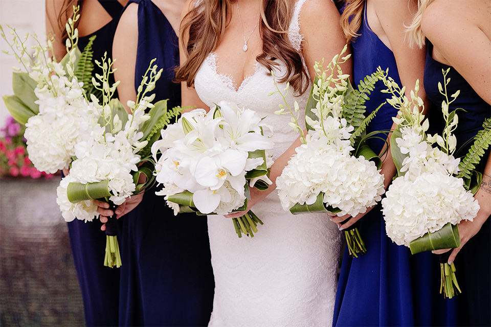 Huntington beach wedding at the hilton waterfront resort bride form fitting lace gown with a plunging neckline and thin straps with lace detail and low back design holding white and green floral bridal bouquet with bridesmaids long navy blue dresses with white and green floral bouquets close up
