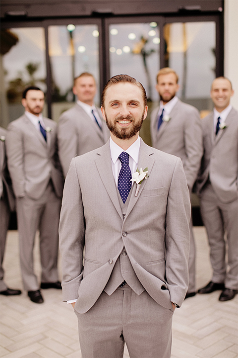 Huntington beach wedding at the hilton waterfront resort groom and groomsmen heather grey notch lapel suits with matching vests and white dress shirt with long navy blue patterned tie and white floral boutonnieres standing with hands in pockets