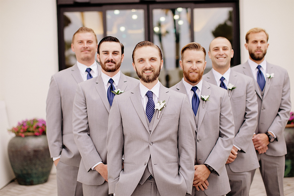 Huntington beach wedding at the hilton waterfront resort groom and groomsmen heather grey notch lapel suits with matching vests and white dress shirt with long navy blue patterned tie and white floral boutonnieres standing with hands crossed