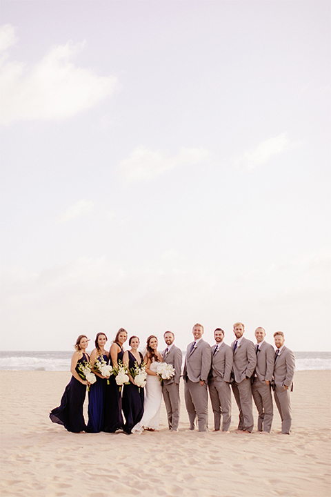 Huntington beach wedding at the hilton waterfront resort bride form fitting lace gown with a plunging neckline and thin straps with lace detail and low back design with groom heather grey notch lapel suit with matching vest and white dress shirt with long navy blue patterned tie and white floral boutonniere with wedding party bridesmaids long navy dresses with white floral bouquets and groomsmen heather grey suits with long navy blue ties
